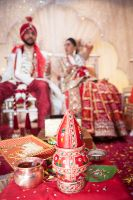 Sona and Amer seated at wedding by Resh Rall Wedding Photography, Leeds