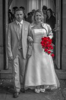 Bride and groom leaving church with stunning wedding dress and red bouquet of flowers by Resh Rall wedding photographer in Yorkshire
